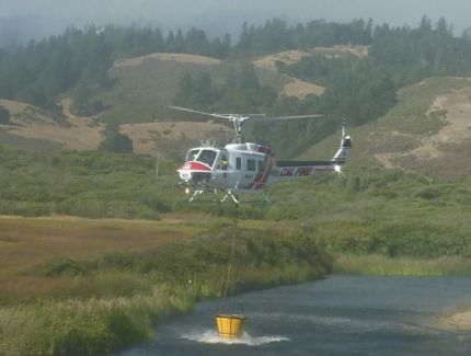 Chopper topping up water for the fires on the hill behind