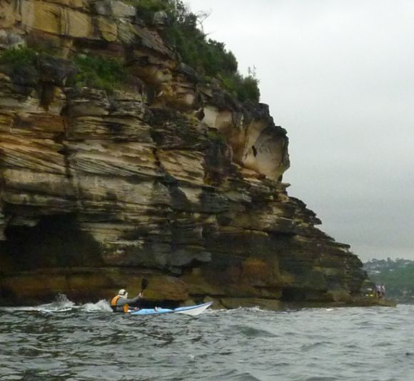 Timbo paddling along the cliff at Middle Head