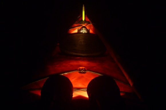 The kayak's front deck lit up by my headlights