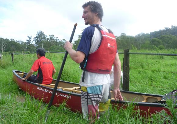 Chris loads up a couple of stranded locals into his canoe