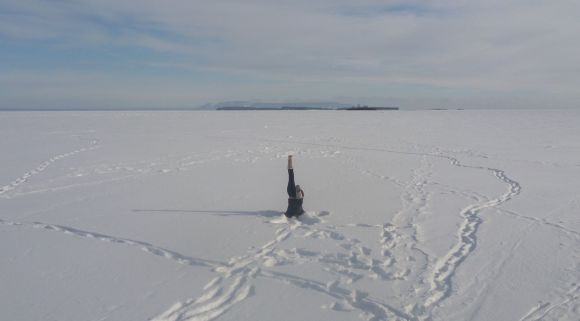 Helen does a head-stand on the frozen surface of Lake Superior