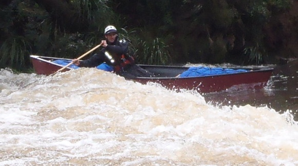 Travis paddling onto the standing wave at the weir