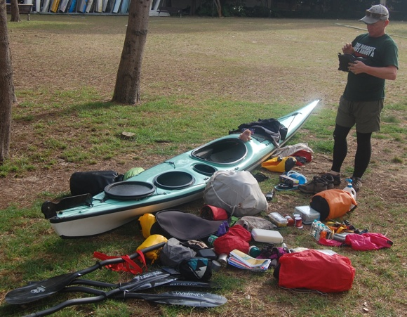 Jason readying his gear as he packs it away into his Nadgee Expedition sea kayak