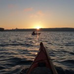 The rising sun and a lone kayak fisherman