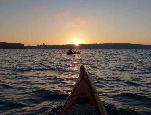 The rising sun and a lone kayak fisherman