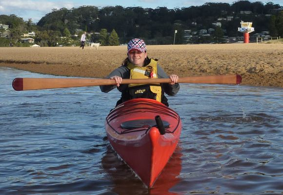 Bec in the kayak with a Greenland paddle in hand