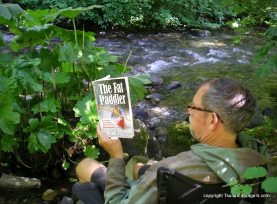 Eric Soares reading The Fat Paddler by a small stream, West Coast USA